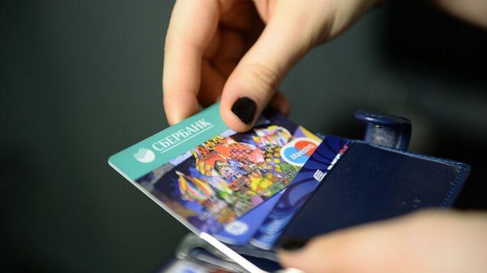 Женщина достает карту из бумажника